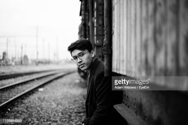Portrait Of Young Man Standing Against Rusty Train
