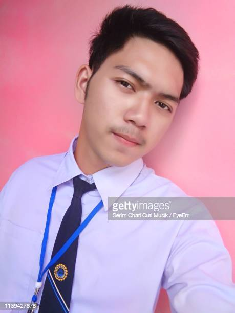 portrait of young man standing against wall - musik stock pictures, royalty-free photos & images