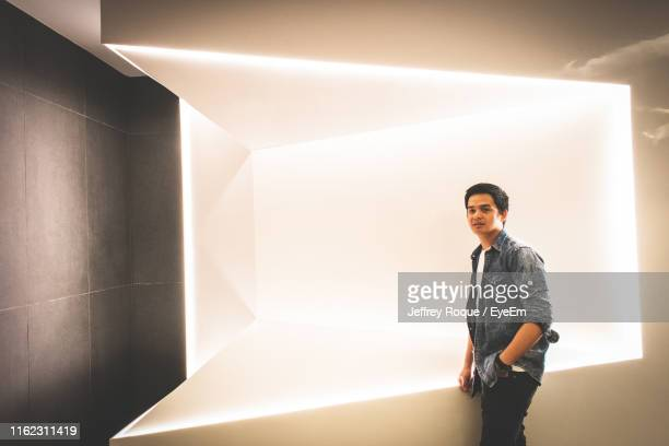 portrait of young man standing against wall - jeffrey roque stock photos and pictures