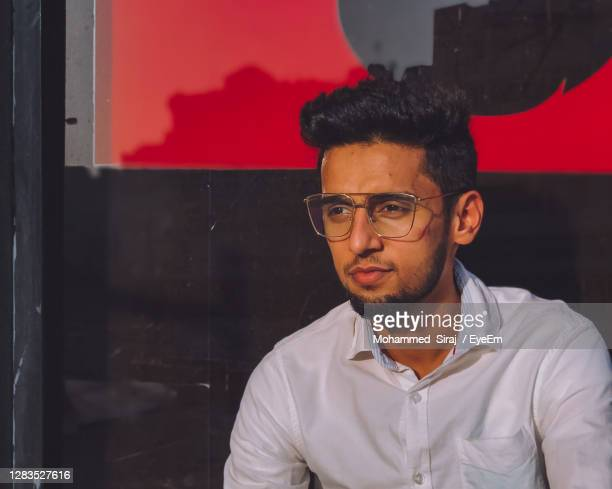 portrait of young man standing against wall - qatar stock pictures, royalty-free photos & images