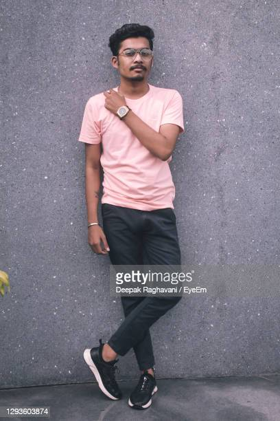 portrait of young man standing against wall - gray shoe stock pictures, royalty-free photos & images