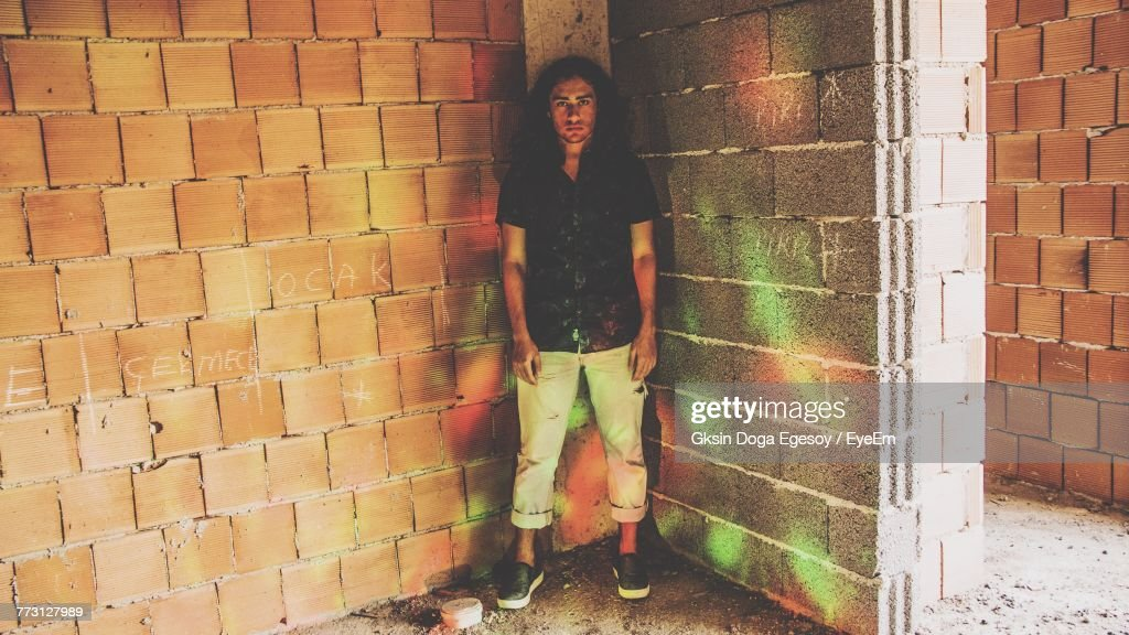 Portrait Of Young Man Standing Against Wall : Photo