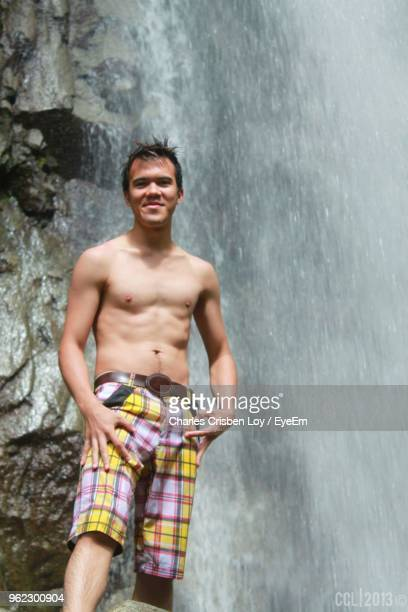 Portrait Of Young Man Standing Against Waterfall