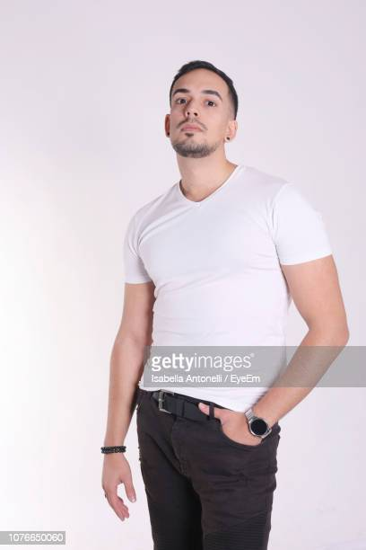 portrait of young man standing against white background - tre quarti foto e immagini stock