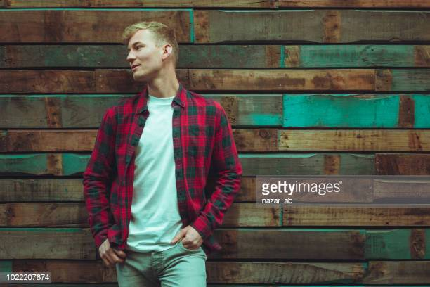 Portrait of young man standing against wooden wall.