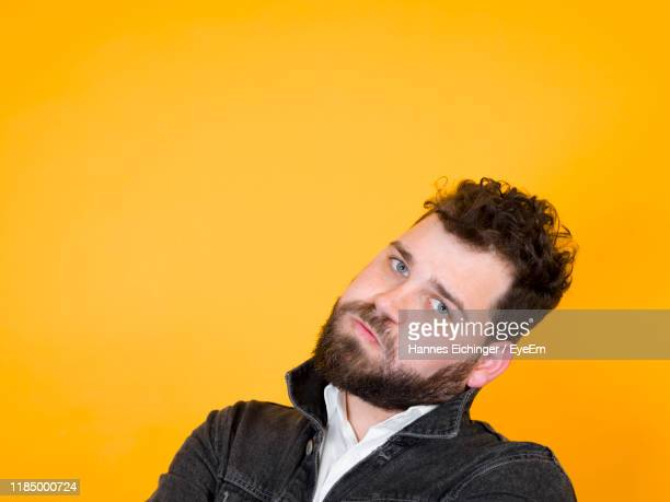 portrait of young man standing against yellow background - head cocked stock pictures, royalty-free photos & images