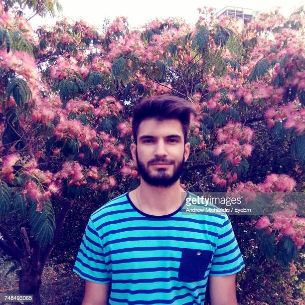 Portrait Of Young Man Standing Amidst Pink Flowers Blooming At Park