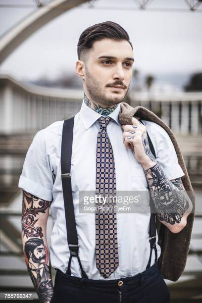 portrait of young man standing in city - men fashion stock photos and pictures