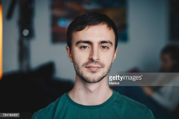 portrait of young man standing in college dorm room - 20 24 jaar stockfoto's en -beelden