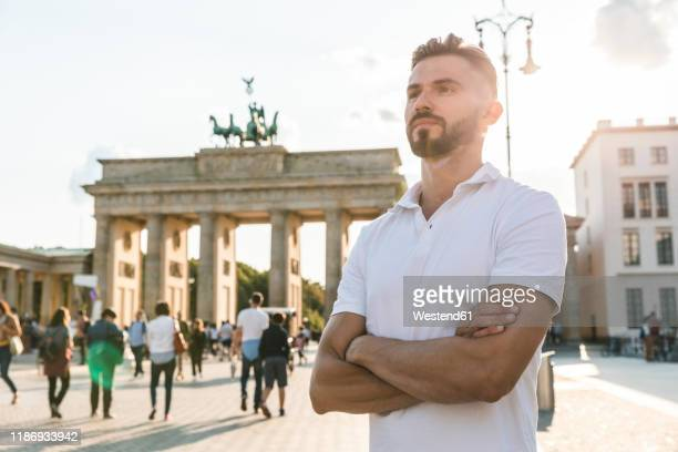 portrait of young man standing in front of brandenburger tor at backlight, berlin, germany - polo shirt stock pictures, royalty-free photos & images