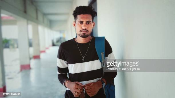portrait of young man standing near wall - college admission stock pictures, royalty-free photos & images