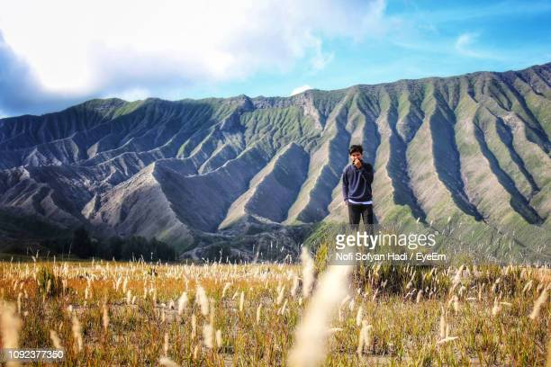 Portrait Of Young Man Standing On Field Against Mountain