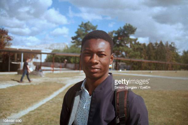 portrait of young man standing on field against sky - marne stock pictures, royalty-free photos & images