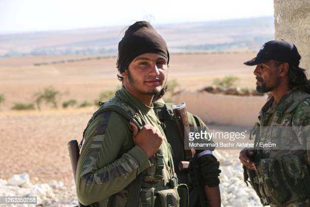 portrait of young man standing on land - extremism stock pictures, royalty-free photos & images