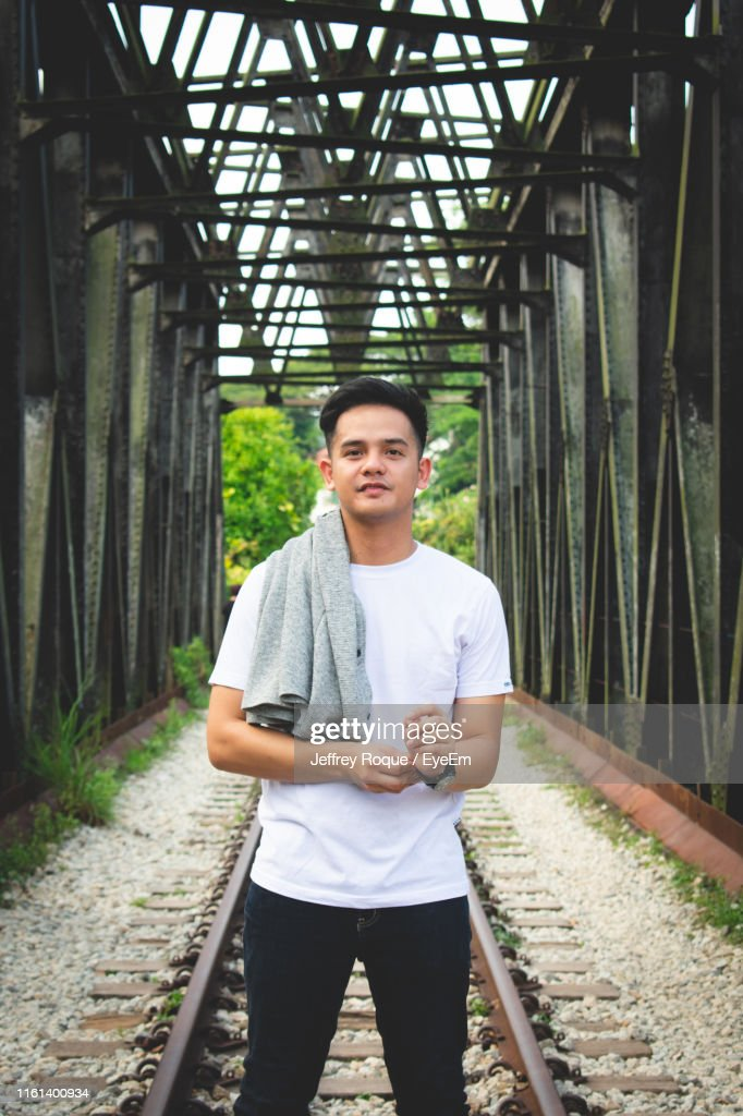 Portrait Of Young Man Standing On Railroad Track : Stock Photo