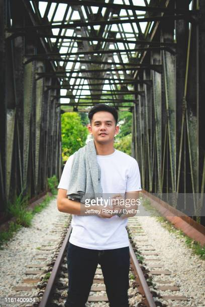 portrait of young man standing on railroad track - jeffrey roque stock photos and pictures
