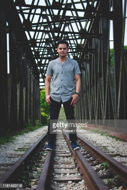 portrait of young man standing on railroad tracks - jeffrey roque stock photos and pictures