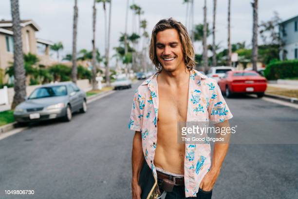 portrait of young man standing on suburban street - fully unbuttoned stock pictures, royalty-free photos & images
