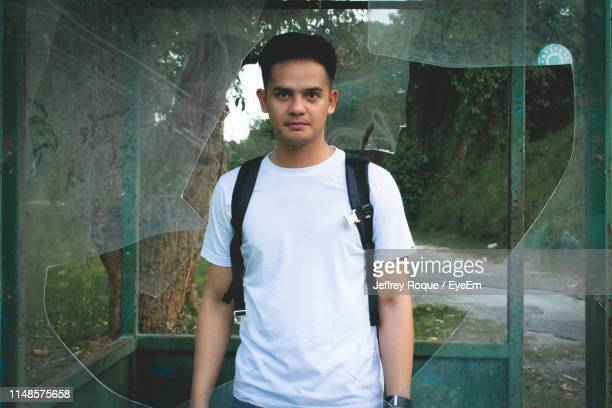 portrait of young man standing outdoors - jeffrey roque stock photos and pictures
