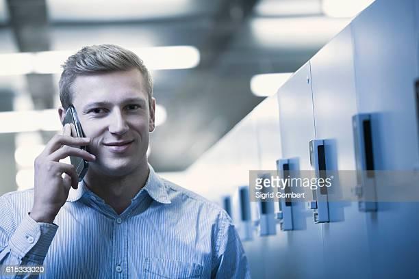 portrait of young man talking on mobile phone in locker room, freiburg im breisgau, baden-württemberg, germany - sigrid gombert stock-fotos und bilder