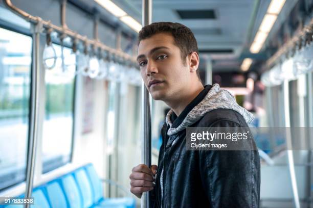 Portrait of young man traveling by subway train looking away