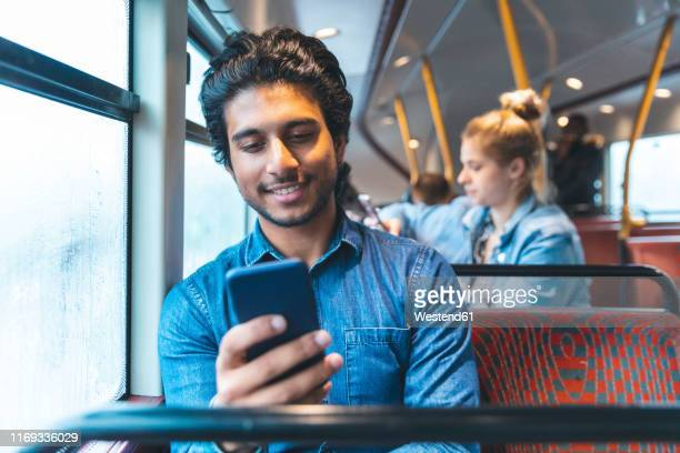 portrait of young man travelling by bus looking at cell phone, london, uk - indian ethnicity stock pictures, royalty-free photos & images