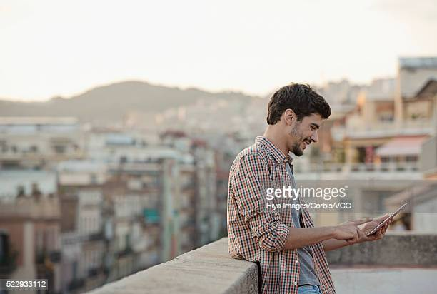 portrait of young man using digital tablet on roof terrace - só um homem imagens e fotografias de stock