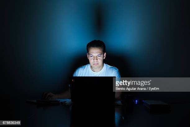 Portrait Of Young Man Using Laptop In Dark Room