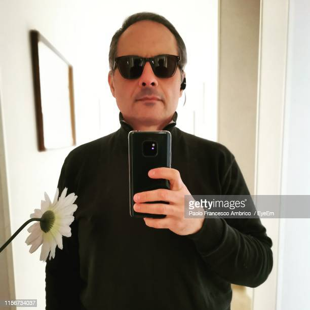 portrait of young man using mobile phone while standing in front of mirror - mirror selfie stock pictures, royalty-free photos & images