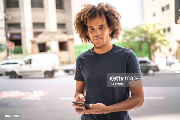 retrato do homem novo que usa o telefone na rua - só um homem jovem - fotografias e filmes do acervo