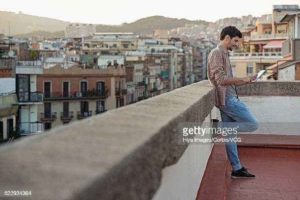 Portrait of young man using tablet computer, leaning against parapet of roof terrace
