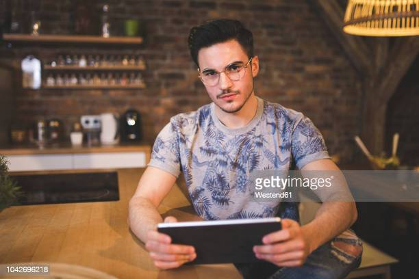 portrait of young man using tablet in kitchen at home - arrogance stock pictures, royalty-free photos & images