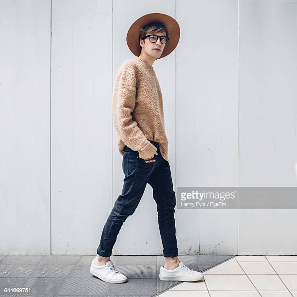 portrait of young man walking on footpath against wall - fashionable stock pictures, royalty-free photos & images