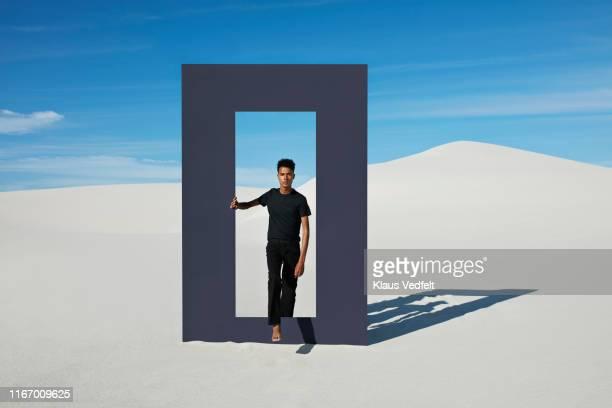 portrait of young man walking through door frame at desert - pantalones negros fotografías e imágenes de stock