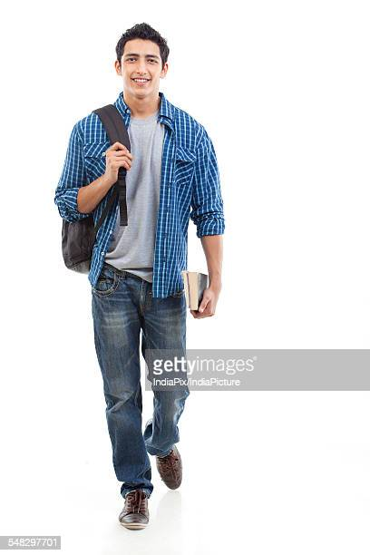 portrait of young man walking with bag and book over white background - handsome asian guy stock photos and pictures