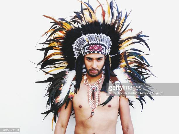 Portrait Of Young Man Wearing Apache Headdress Against White Background
