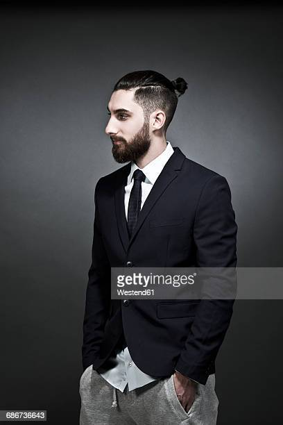 portrait of young man wearing black jacket and jogging pants in front of grey background - man bun stock pictures, royalty-free photos & images