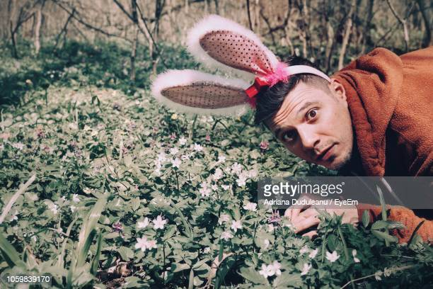 portrait of young man wearing bunny ear headband in park - easter bunny man stock pictures, royalty-free photos & images