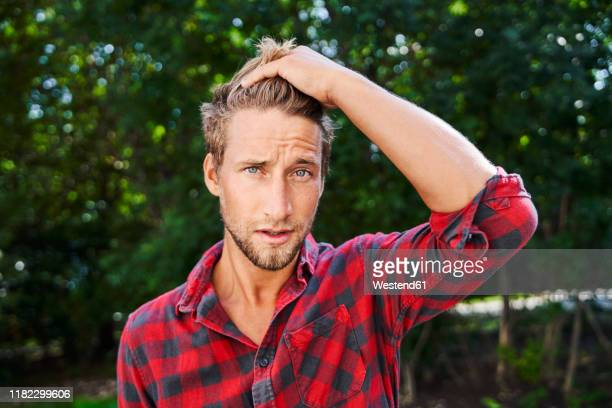 portrait of young man wearing checkered shirt outdoors - plaid shirt stock pictures, royalty-free photos & images