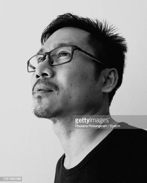 portrait of young man wearing eyeglasses against white background - black and white stock pictures, royalty-free photos & images