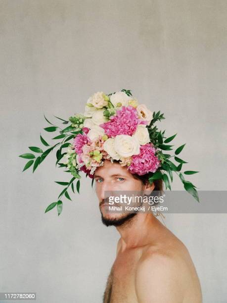 portrait of young man wearing flowers against wall - art bildbanksfoton och bilder