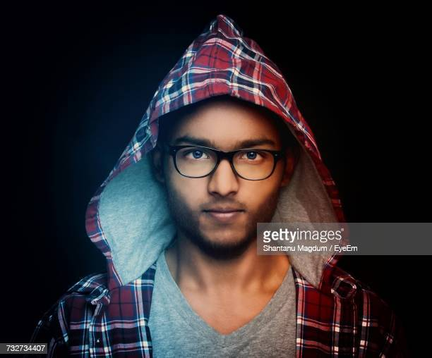 Portrait Of Young Man Wearing Hooded Plaid Shirt Against Black Background