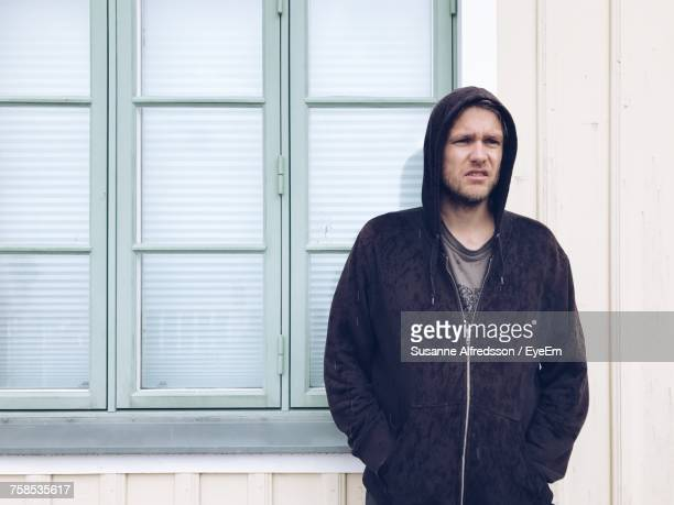 Portrait Of Young Man Wearing Hooded Shirt Against Window