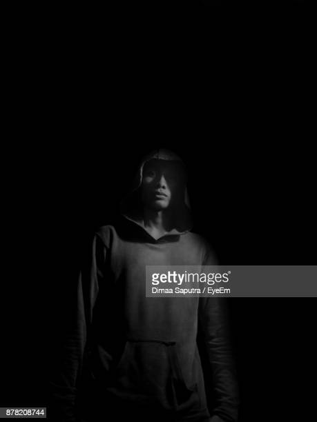 Portrait Of Young Man Wearing Hooded Shirt Standing Against Black Background