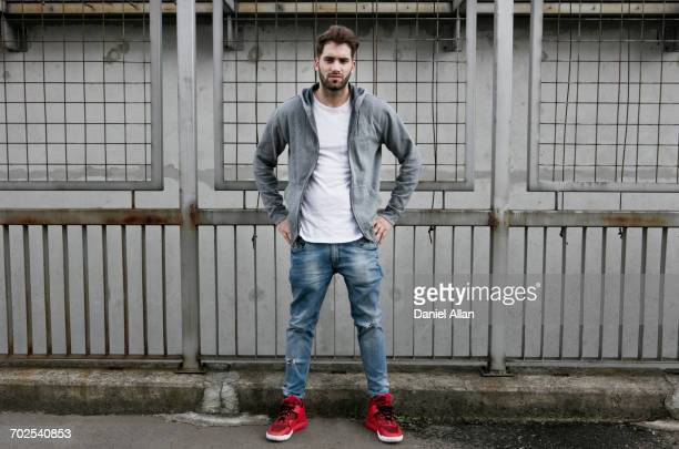 portrait of young man, wearing hooded top, hands on hips - パーカー服 ストックフォトと画像