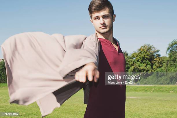 portrait of young man wearing jacket and standing on grassy field - coat ストックフォトと画像