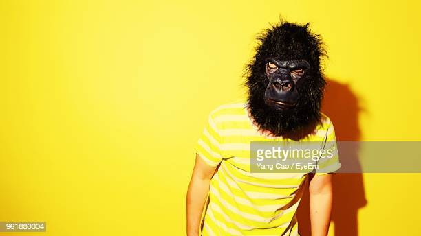 portrait of young man wearing mask while standing against yellow background - monkey man stock pictures, royalty-free photos & images