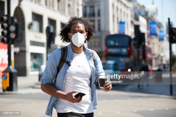 portrait of young man wearing protective mask crossing the street, london, uk - virus organism stock pictures, royalty-free photos & images