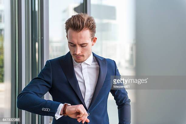 Portrait of young man wearing suit checking the time