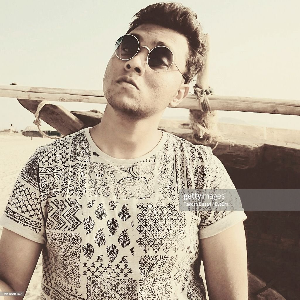 49c9b4663e46 Portrait Of Young Man Wearing Sunglasses By Boat At Beach : Stock Photo